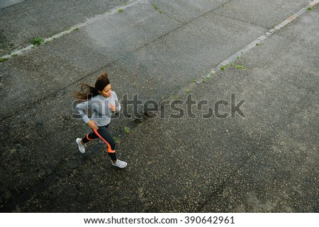 Top view of fit female athletes running on rainy day. Woman exercising outdoor on urban asphalt.