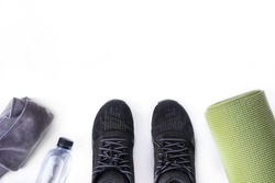 Top view of fitness accessories on white background with copy space, black sneaker, bottle, towel and green yoga mat