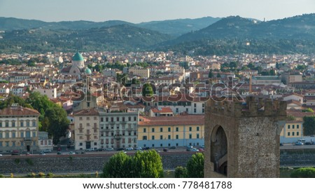 Top view of Florence city timelapse at sunrise with arno river bridges and historical buildings, mountains on background. Green trees, blue cloudy sky at summer day #778481788