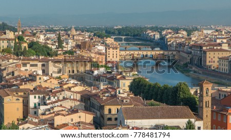 Top view of Florence city timelapse at sunrise with arno river bridges and historical buildings, mountains on background. Green trees, blue cloudy sky at summer day #778481794