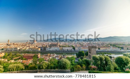 Top view of Florence city timelapse at sunrise with arno river bridges and historical buildings, mountains on background. Green trees, blue cloudy sky at summer day #778481815
