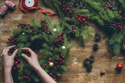 top view of florist hands making Christmas wreath on wooden tabletop