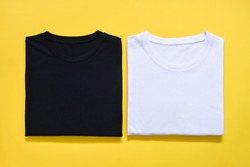 top view of folded black and white color t-shirt on yellow background, copy space, flat lay
