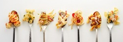 Top view of forks and spoons with different types of yummy pasta placed in row on gray background