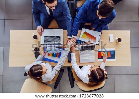 Top view of four successful business people sitting at table and stacking hands. On table are charts and statistics for stock market.