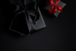 Top view of free space card for text with black gift box isolated on black background. Shopping concept boxing day and black Friday composition.