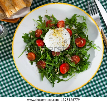 Top view of fresh arugula salad with cherry tomatoes, soft Italian cheese burrata, pine nuts and savoury sauce