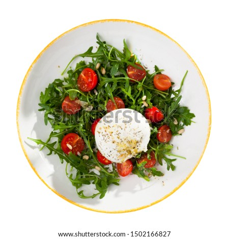 Top view of fresh arugula salad with cherry tomatoes, soft Italian cheese burrata, pine nuts and savoury sauce. Isolated over white background