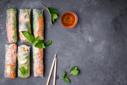 Top view of fresh assorted Asian spring rolls set with shrimps, vegetables, fruits, copy space