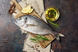 Top view of fresh fish dorado or gilt-head bream with lemon, olive oil and spices as pepper, rosemary on wooden cutting board and brown concrete background
