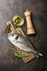 Top view of fresh fish dorado or gilt-head bream with olive oil and spices as pepper, rosemary on wooden cutting board and brown concrete background