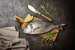 Top view of fresh fish dorado or gilt-head bream with spices as pepper, rosemary, lemon on wooden cutting board and brown concrete background