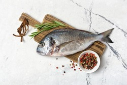 Top view of fresh fish dorado or gilt-head bream with spices as pepper, rosemary on wooden cutting board and white marble background