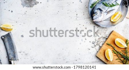 Top view of fresh fish in pan with lemon and rosemary on rustic white kitchen table. Sea food dinner preparation from above. Luxury restaurant menu design banner with seafood on textured backgrond.