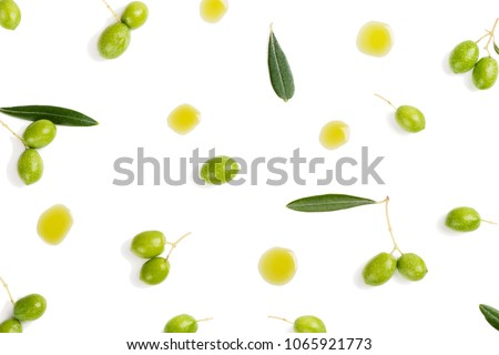 Top view of fresh green olive fruits with leaves and puddles of olive oil isolated on white background.