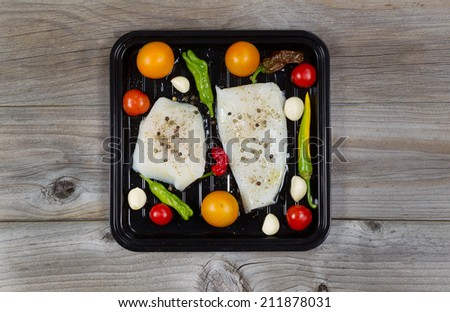 Top view of fresh raw Cod Fish Fillets in cooking pan with tomatoes, garlic, peppers and peppercorn salt on rustic wooden boards