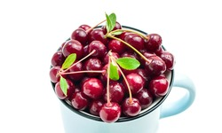 Top view of fresh red ripe cherry berries with sprigs and leaves in a blue mug isolated on white background. Sweet tasty fruits and water droplets in a cup close-up. Healthy food. Summertime vitamins.