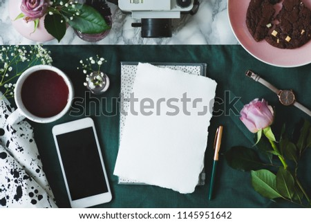 Top view of fresh rose placed next to blank paper on marble desk with green cloth with empty screen phone, cup with tea and watch