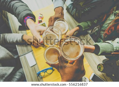Top view of friends cheering with home brew in pub bar restaurant - Young people hands toasting and beers half pint - Friendship and party concept - Warm matte filter - Focus on bottom hand