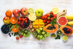 Top view of fruits, strawberries, blueberries, mango, orange, grapefruit, banana, apple, grapes, kiwis on the white background, copy space for text, selective focus