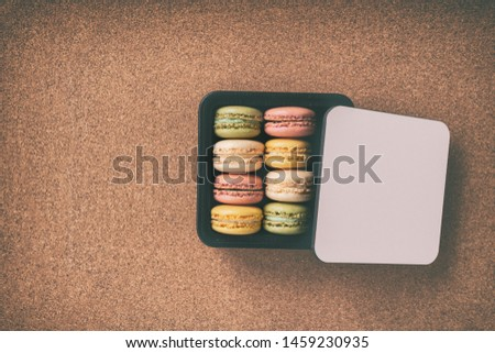 Top view of gift box macaroons wrapped in giftbox on tabletop. Vignette background. #1459230935