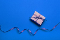 Top view of gift box wrapped in kraft paper and a gold ribbon on a blue background, flat lay
