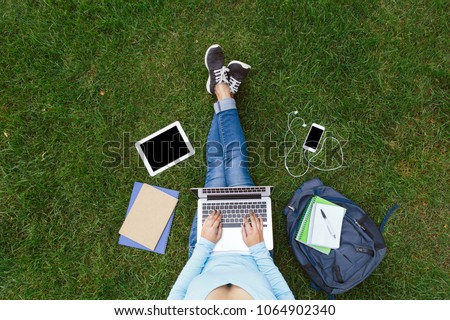 Top view of girl sitting in park on the green grass with laptop, tablet, smartphone with earphones and backpack. Copy space on screens. Flat lay