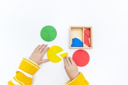 Top view of girls hand is playing and sorting a puzzle of colored wooden geometric shapes in montessori school. Concept of using a mathematical geometry learning resources for children education.
