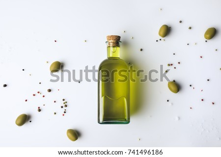 Top view of glass bottle with olive oil and olives isolated on white