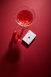 top view of glass of cocktail near deck of cards and dice on red background