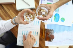 Top view of glassful with alcoholic beverage with ice-cubes in male hands. Colleague sitting at table in office celebrating signing profitable contract. Biz negotiations concept. Blurred background
