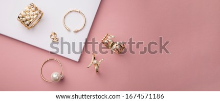 Top view of golden and pearl bracelets on pink and white background with copy space