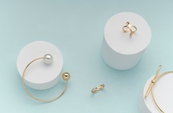 Top view of golden bracelets and rings on on white cylinders on bright pastel color background