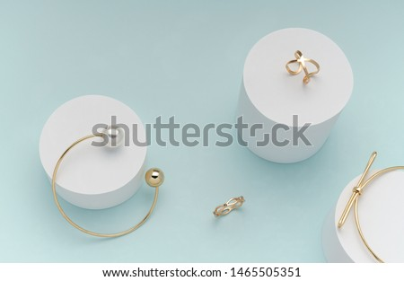 Top view of golden bracelets and rings on on white cylinders on bright pastel color background stock photo