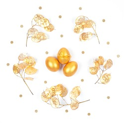 Top view of golden colored Easter eggs with dry flowers frame and confetti isolated on white background. Greeting card. Flat lay