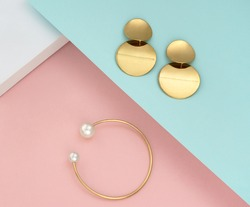 Top view of golden with pearls bracelet and earrings pair on pastel colors papers