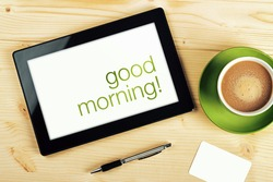 Top View of Good Morning Message on Tablet Computer Screen on Office Table.