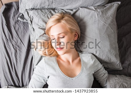 Top view of gorgeous restful european woman with blonde hair, fresh clean skin having sleep time and sweet dreams, lying on gray fresh linen, resting in bedroom. Bedtime, healthy dream concept. #1437923855