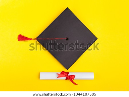 Top view of graduation mortarboard and diploma isolated on yellow background, education concept