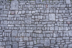 Top view of granite cobblestoned pavement background. Full frame of irregular small and big cobbles in lines. Natural stone textured background