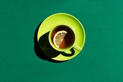 top view of green cup and saucer with black tea with yellow lemon or coffee on the dark green background. copy space.