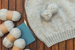 Top view of grey knitting yarns, notebook, pencil and a part of knitted sweater on brown wooden background. Hobby and needlecraft at home