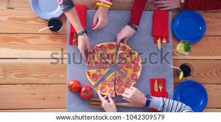 Top view of group of people having dinner together while sitting at wooden table. Food on the table. People eat fast food. #1042309579