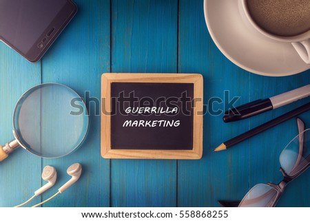Shutterstock Top view of GUERRILLA MARKETING written on the chalkboard,business concept.chalkboard,smart phone,cup,magnifier glass,glasses pen on wooden desk.