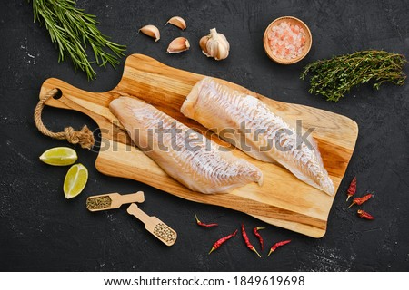 Top view of haddock fillet with seasoning on wooden cutting board ストックフォト ©