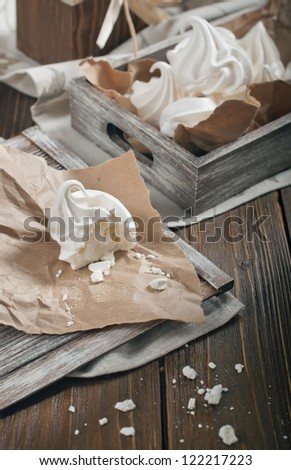Top view of half of meringue and crumbs on paper and wooden box with meringues on dark wooden background