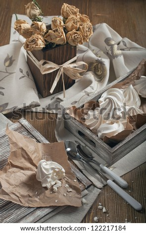 Top view of half of meringue and crumbs on paper, wooden box with meringues and dry roses in square vase on dark wooden background