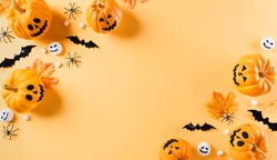 Top view of Halloween crafts, orange pumpkin, white ghost, bat and spider on orange background with copy space for text. halloween concept.