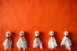 Top view of Halloween crafts, paper ghost on orange paper background with copy space for text. halloween concept.