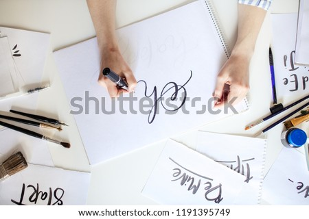 Top view of hand of girl with pen writes on paper with ink #1191395749